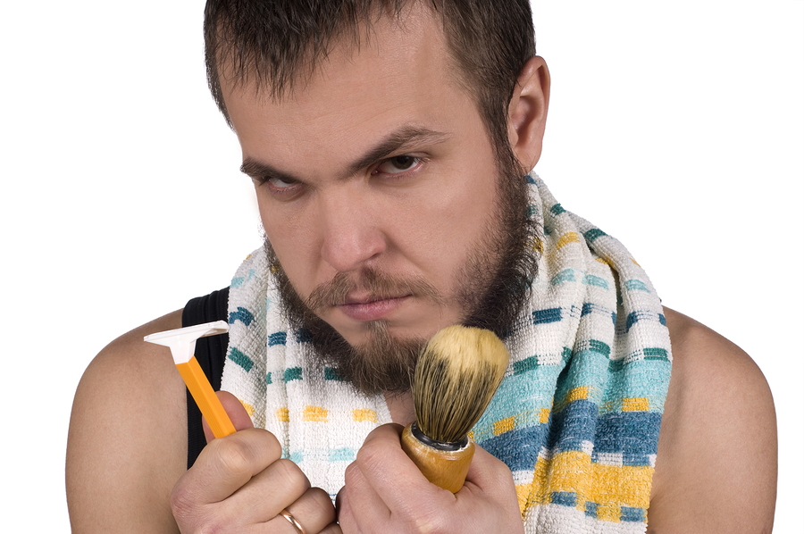 Young man with beard holding a razor and shaving brush in hands