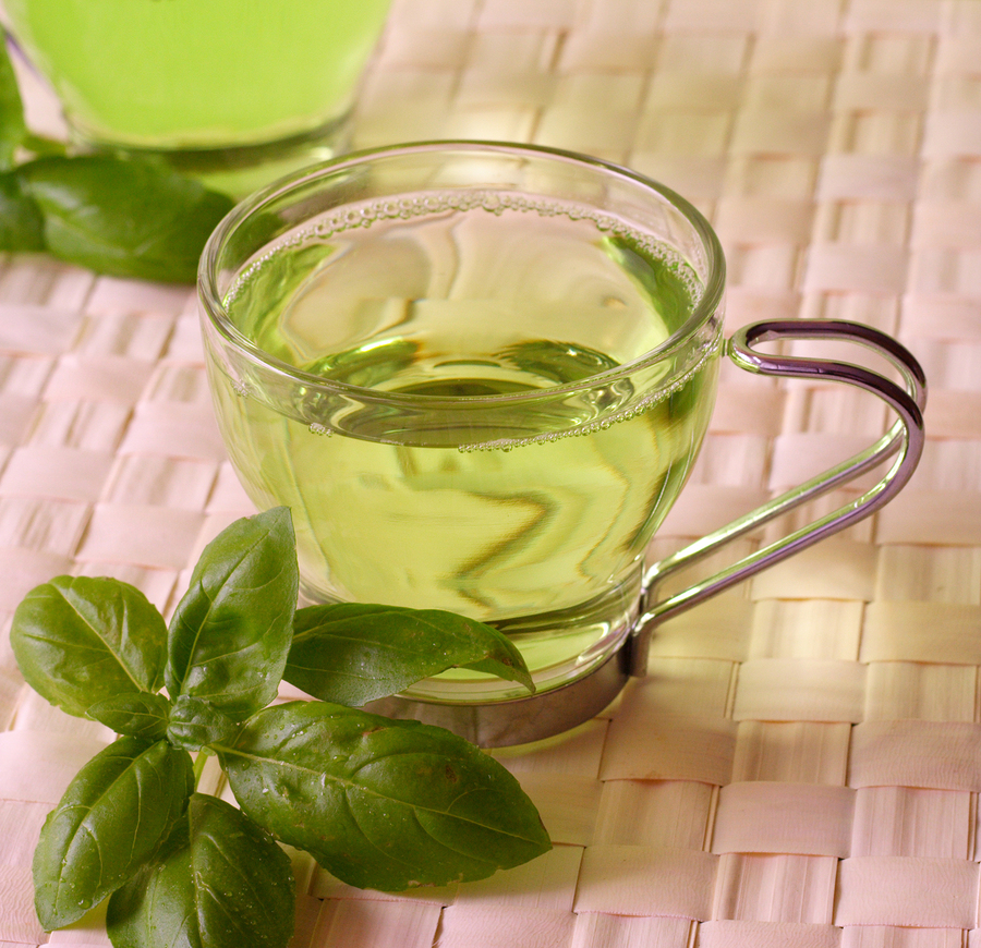 A clear cup of green tea with herbs up close