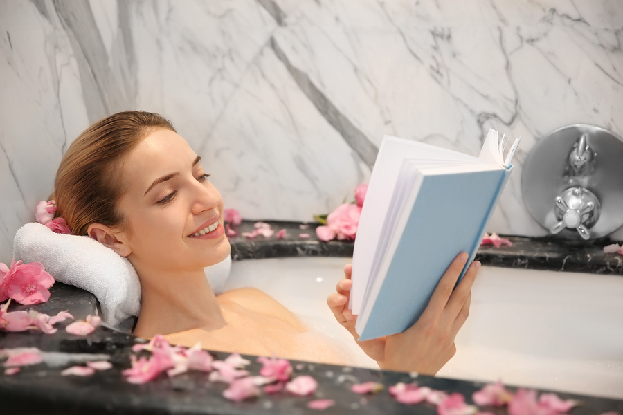 A young woman enjoying a book in a bath.